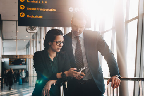 Business couple using mobile phone in airport terminal - MASF07821