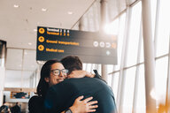 Smiling businesswoman embracing businessman in airport terminal - MASF07824