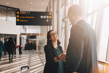 Smiling businesswoman shaking hand with businessman in airport terminal - MASF07827