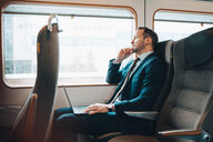 Thoughtful businessman with laptop traveling in train - MASF07857