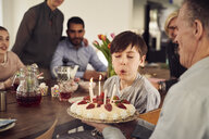 Boy blowing candles on birthday cake while enjoying in party with family at home - MASF07920