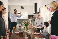 Man photographing boy with family during birthday party through smart phone - MASF07932