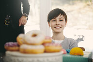 Portrait of smiling boy sitting by grandmother at dining table with donuts in foreground - MASF07935