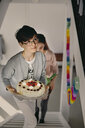Boy carrying birthday cake while climbing up steps with sister at home - MASF07938