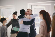 Smiling senior father embracing man while standing by family at doorway - MASF07947