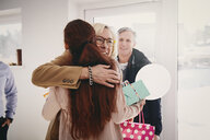 Smiling grandmother embracing granddaughter against door at home - MASF07950