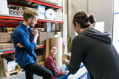 Colleagues discussing while having coffee in distribution warehouse - MASF07953