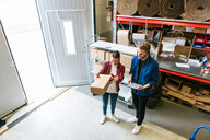High angle view of male and female coworkers examining cardboard box at distribution warehouse - MASF07959