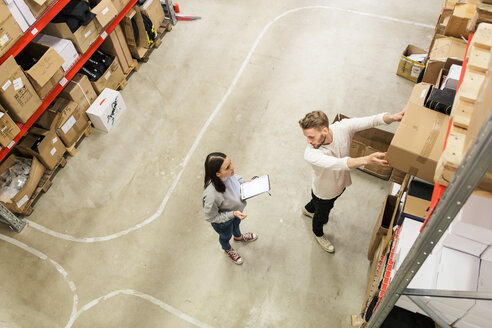 Colleagues discussing while examining cardboard boxes in industry - MASF07989