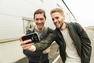 Smiling coworkers taking selfie through mobile phone outside industry - MASF08004