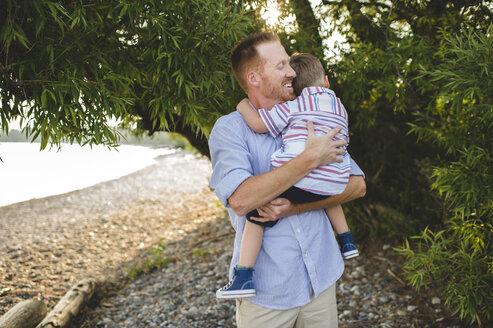 Father and young son hugging at Lake Ontario, Oshawa, Canada - CUF20908