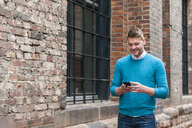 Young man using mobile phone beside brick building - CUF20995