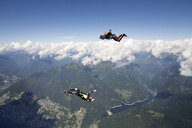 Freestyle skydiving team training together. One man  performing air-ballet, another jumper is filming with video camera on helmet, Locarno, Tessin, Switzerland - CUF21010