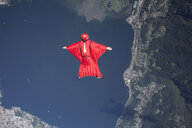 Wingsuit skydiver pilot flying over lake, Locarno, Tessin, Switzerland - CUF21013