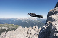 Wingsuit BASE jumper jumping from cliff, Italian Alps, Alleghe, Belluno, Italy - CUF21016
