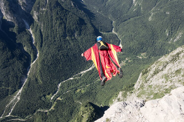 Wingsuit BASE jumper is flying down, Italian Alps, Alleghe, Belluno, Italy - CUF21019