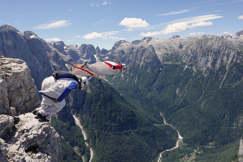 BASE jumping wingsuit pilots are jumping together from a cliff and down the valley, Italian Alps, Alleghe, Belluno, Italy - CUF21022
