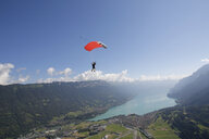Male sky diver with parachute over lake, Interlaken, Berne, Switzerland - CUF21025