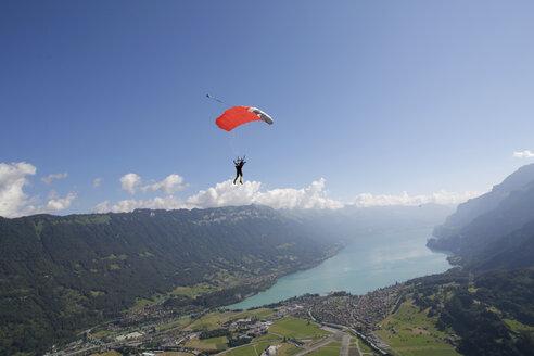 Male sky diver with parachute over lake, Interlaken, Berne, Switzerland - CUF21025
