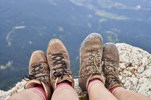 Cropped view of hikers feet wearing hiking books on rocks, Austria - CUF21064