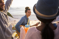 Young adult friends playing guitar and picnicing at beach, Cape Town, Western Cape, South Africa - CUF21118