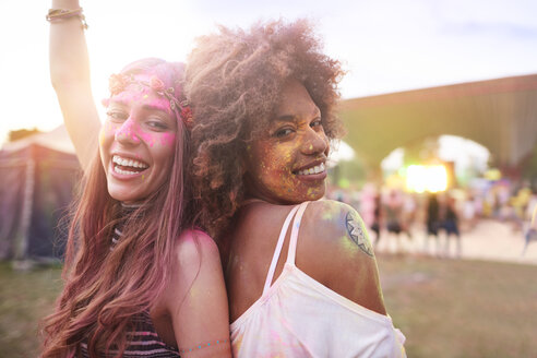 Portrait of two female friends at festival, covered in colourful powder paint - CUF21190