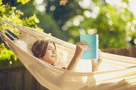 Teenage boy relaxing in garden hammock reading a book - CUF21199