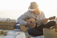 Young man playing guitar on sunlit beach, Cape Town, Western Cape, South Africa - CUF21202