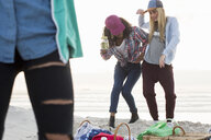 Three young female friends fooling around at beach picnic, Cape Town, Western Cape, South Africa - CUF21205