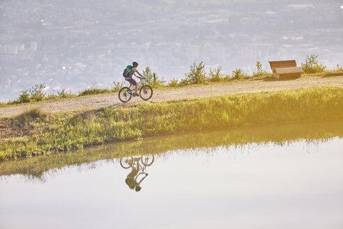 Austria, Tyrol, female mountainbiker at lake in the evening light - CVF00650