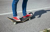 Woman standing on broken skateboard - AIF00502