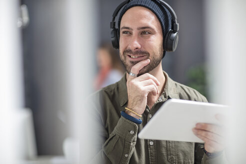 Portrait of smiling young man with headphones and tablet in office - ZEF15524