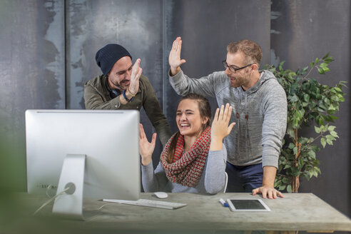 Colleagues happy about good news at desk in office - ZEF15539