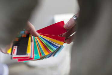 Close-up of man holding colour swatches in office - ZEF15542