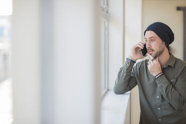 Young man on cell phone at the window in office - ZEF15551