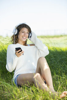 Smiling young woman with earphones and smartphone listening to music - MAEF12623