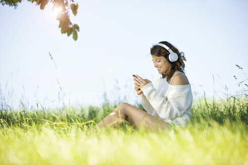 Smiling young woman with earphones and smartphone listening to music - MAEF12626