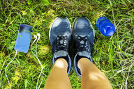 Running shoes, smartphone with earphones, water bottle, overhead view - MAEF12635
