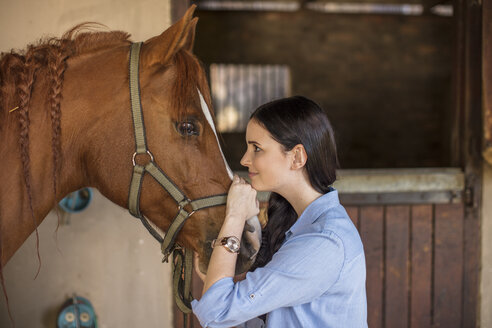 Smiling woman caring for a horse on a farm - ZEF15558