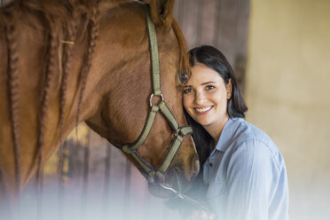 Portrait of smiling woman with a horse on a farm - ZEF15561