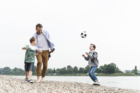 Happy father with two sons and football walking at the riverside - UUF13915