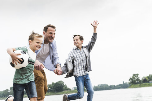 Happy father with two sons and football running at the riverside - UUF13918