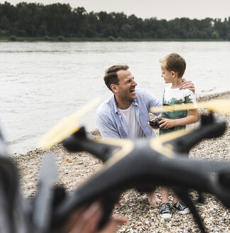 Happy father and son playing with drone at the riverside - UUF13921