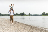 Happy father carrying son on shoulders at the riverside - UUF13924