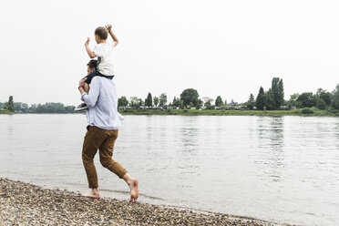 Father carrying son on shoulders at the riverside - UUF13927