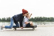Happy boys on skateboard at the riverside - UUF13936