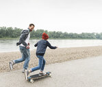Happy father running next to son on skateboard at the riverside - UUF13939