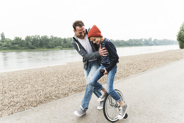 Happy father supporting son on unicycle at the riverside - UUF13942
