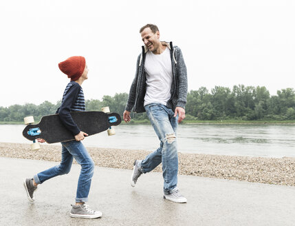 Happy father and son with skateboard at the riverside - UUF13945