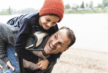 Happy father carrying son on piggyback at the riverside - UUF13951